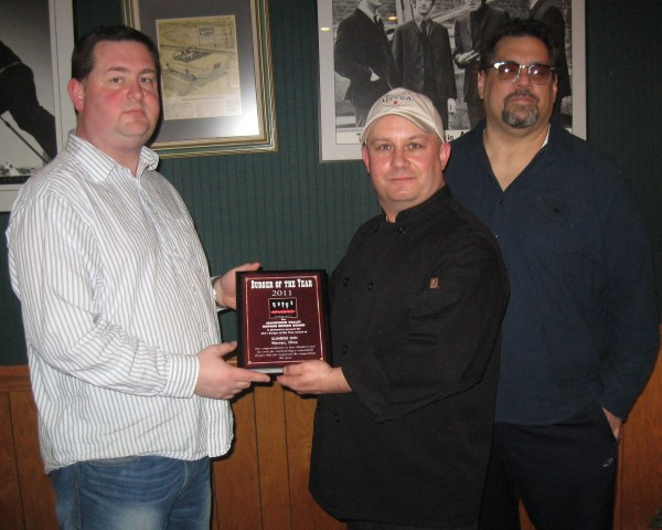 "Board Member Greg Bartholomew, Presents the 2011 Burger of the Year award to Chef Denny ""Stu"" Baumiller and co-owner Dino Haidaris."